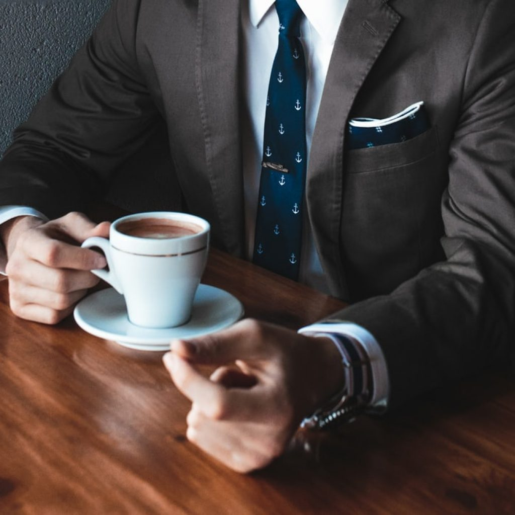 man sitting at table in a suit with a coffee cup