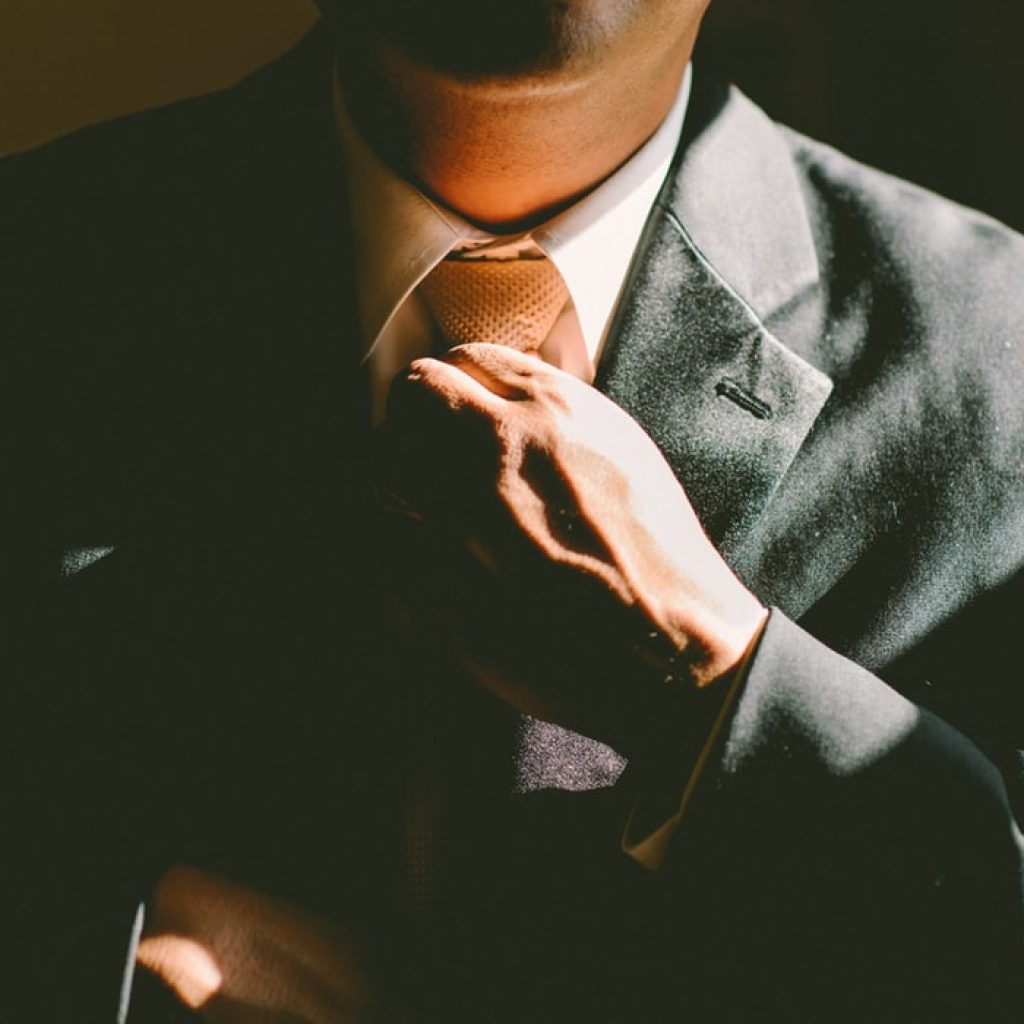man adjusting his tie in a suit