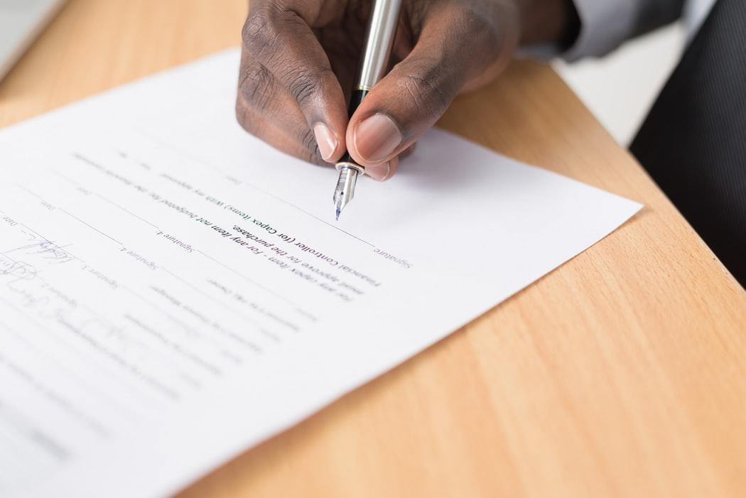 hombre firmando papeleo