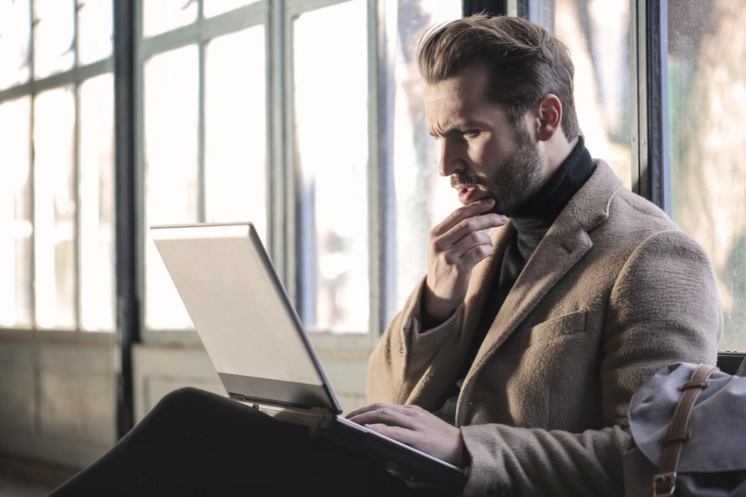 hombre mirando su computadora portátil, preocupado o cuestionando
