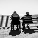 Two people sitting at the beach, one in a wheelchair, black and white