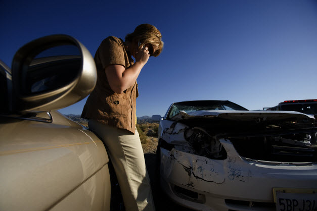 Car Crash Injury Lawyer | Young woman using mobile phone by car wreckage